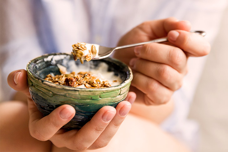young-woman-with-muesli-bowl-girl-eating-breakfast-cereals-with-nuts-picture-id942498878